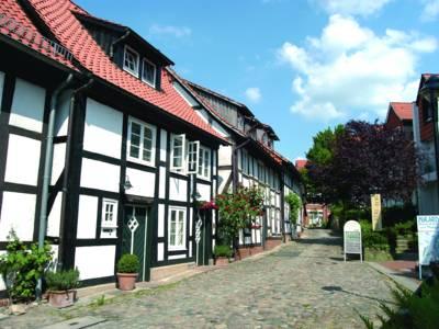 Fachwerkhäuser säumen links und rechts eine mit Natursteinen gepflasterte Gasse.