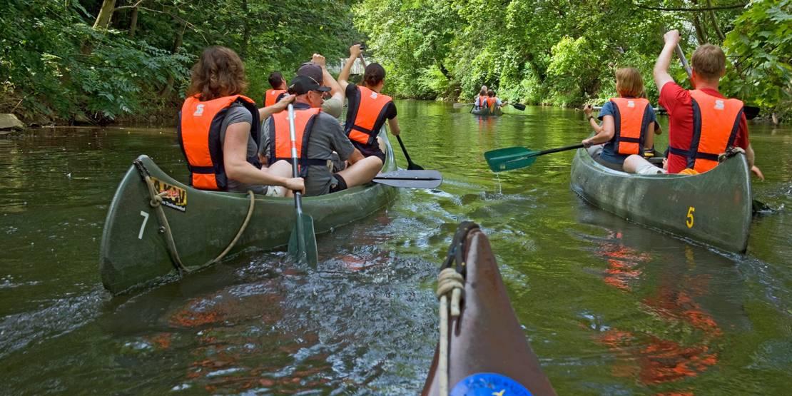 Vier Paddelboote auf einem schmalen Fluß
