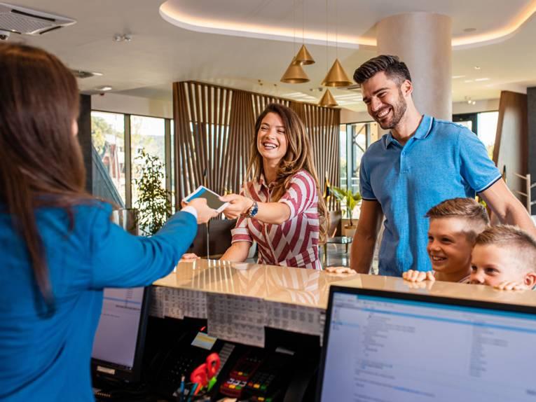 Familie beim Check-In im Hotel
